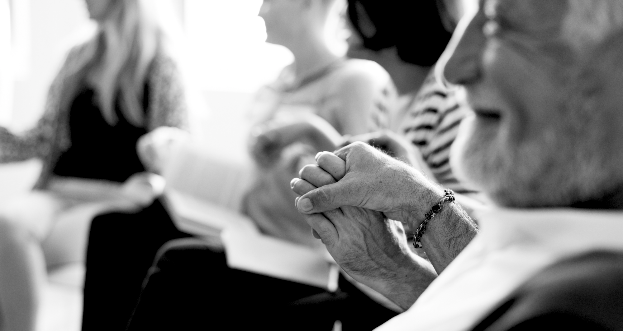 Two older people hold hands in black and white image.