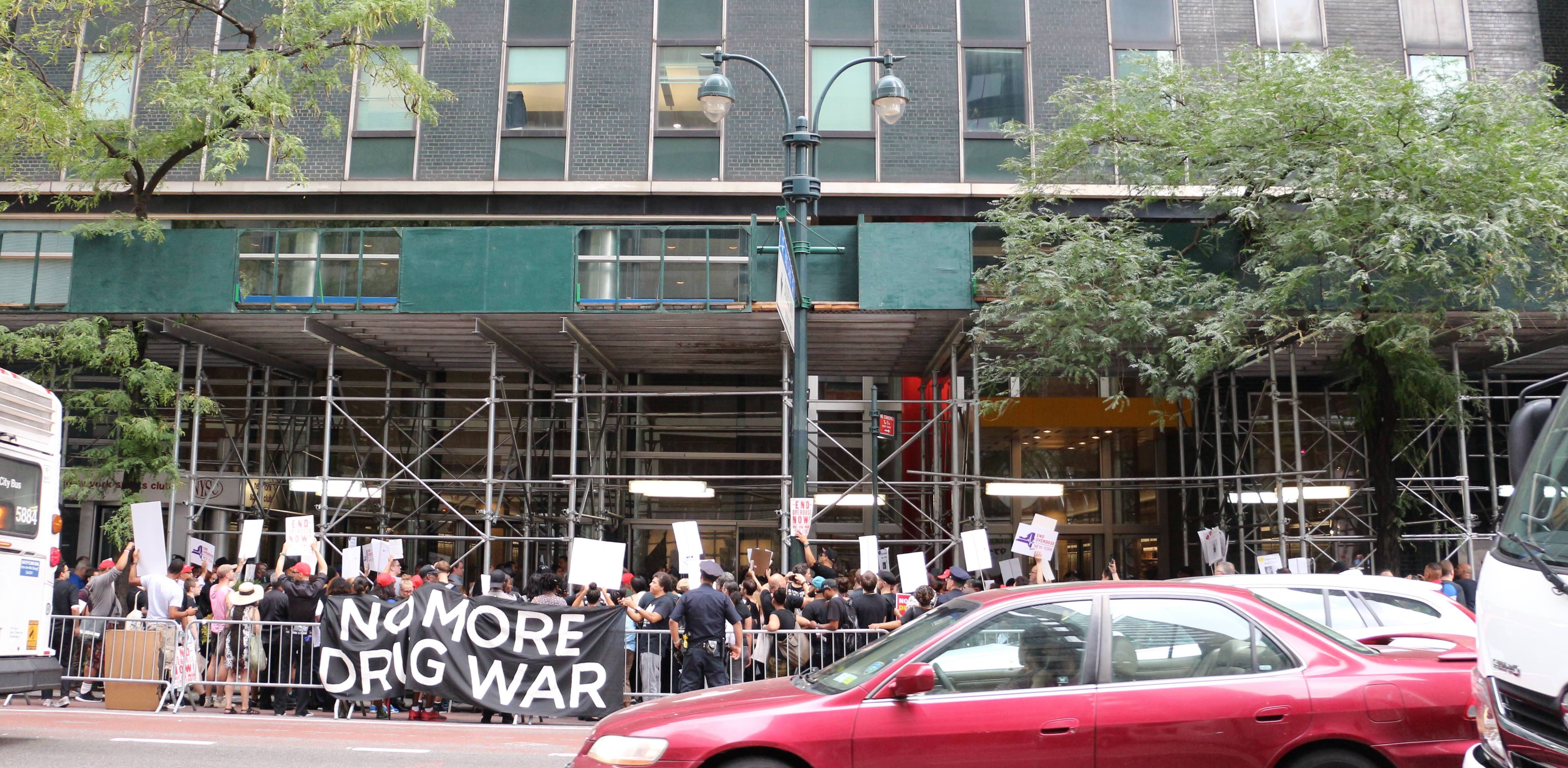 A group of protestors hold a banner outside a building. The banner reads 'NO MORE DRUG WAR'.